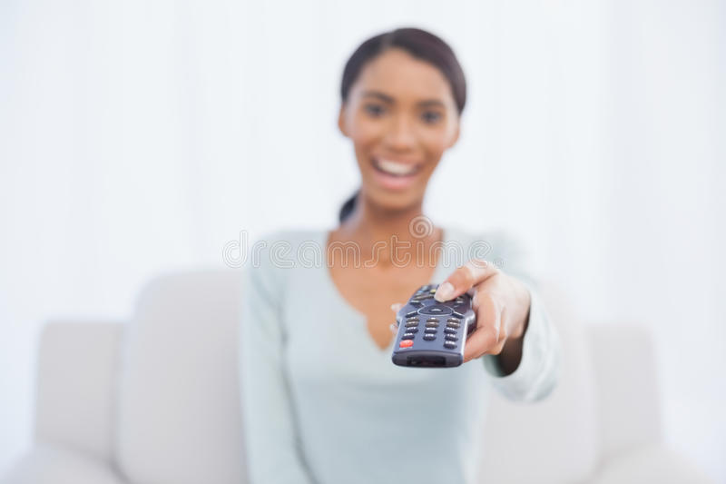 Cheerful woman sitting on sofa changing tv channel royalty free stock photos