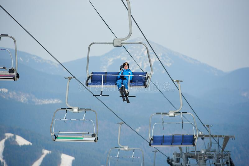 Cheerful woman skier in blue ski suit riding up to the top of the mountain on a cable ski lift with skies. At winter ski resort in the mountains recreation royalty free stock photos