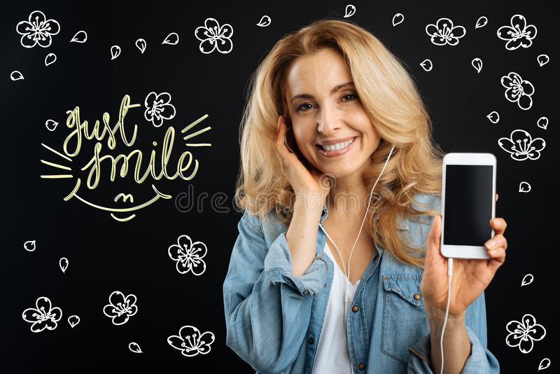 Cheerful woman smiling and showing her new convenient gadget stock photography