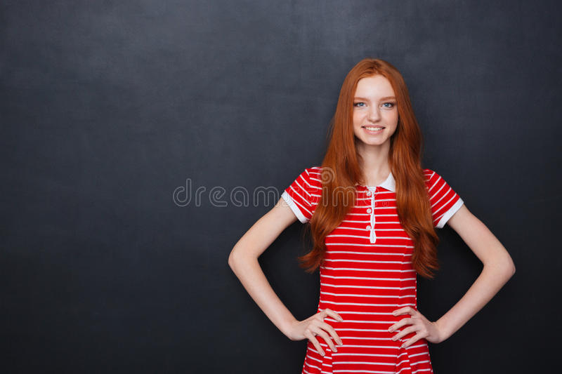 Cheerful woman standing and smiling over blackboard background. Cheerful beautiful redhead young woman smiling with hands on waist over blackboard background stock photo