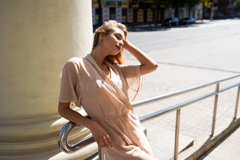Cheerful woman in the street in sunshine light, Attractive blonde girl at summer day royalty free stock image