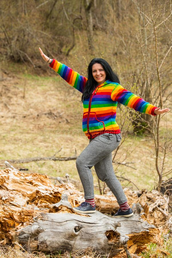 Cheerful woman with stretched hands. Standing on a trunk tree stock image