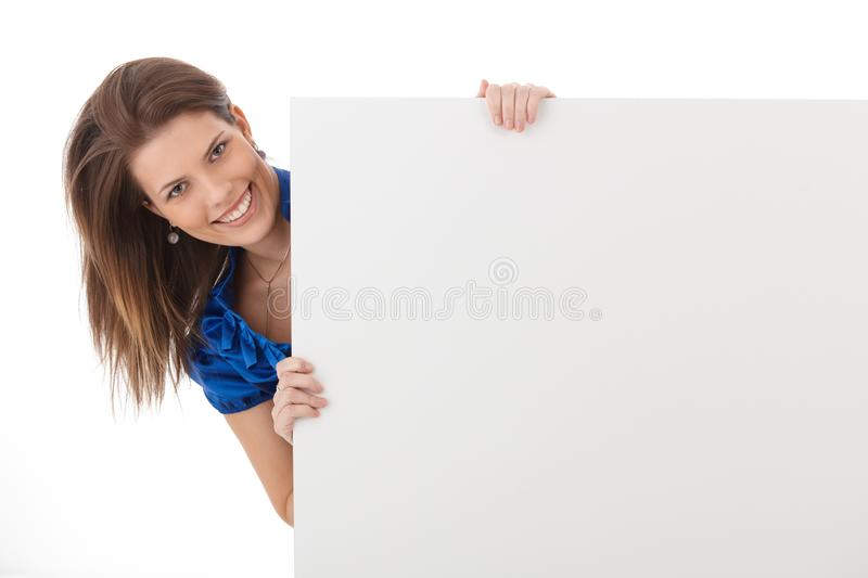 Cheerful woman in studio with blank sheet stock image