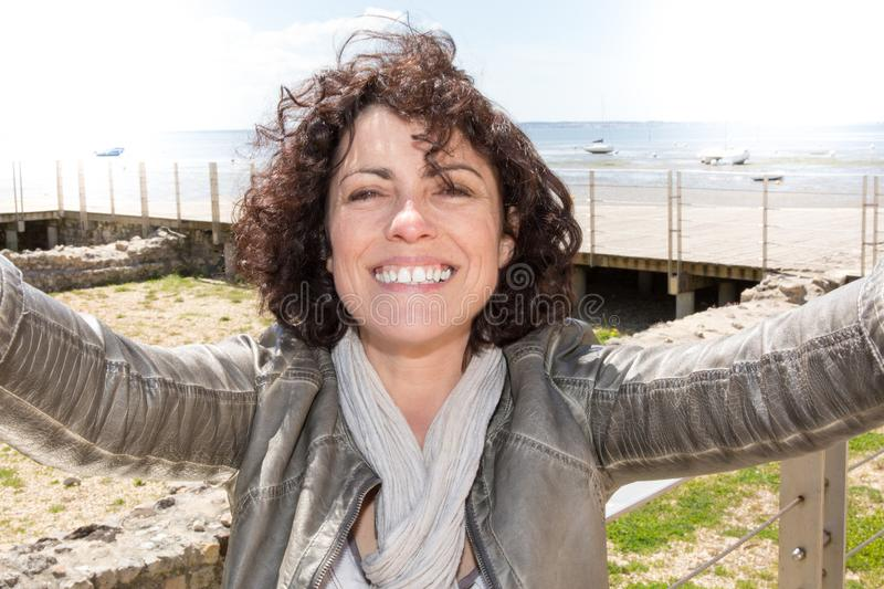Cheerful woman taking a selfie on phone outdoors. Cheerful woman taking a selfie on phone at the beach on a sunny summer day royalty free stock image