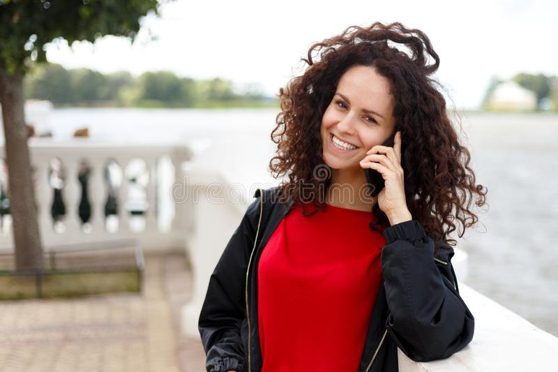 Cheerful woman talking on the phone in the street, wearing a red and black clothes, over sea background. Copy space. stock images