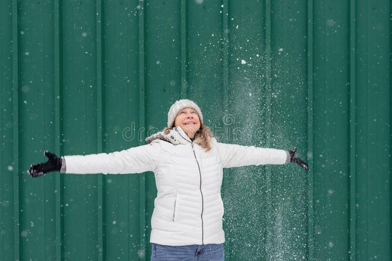 Smiling woman playing in fresh snow outside royalty free stock images