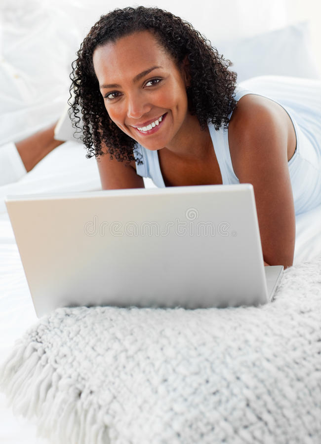 Download Cheerful Woman Using A Laptop On Her Bed Stock Image - Image: 12973745