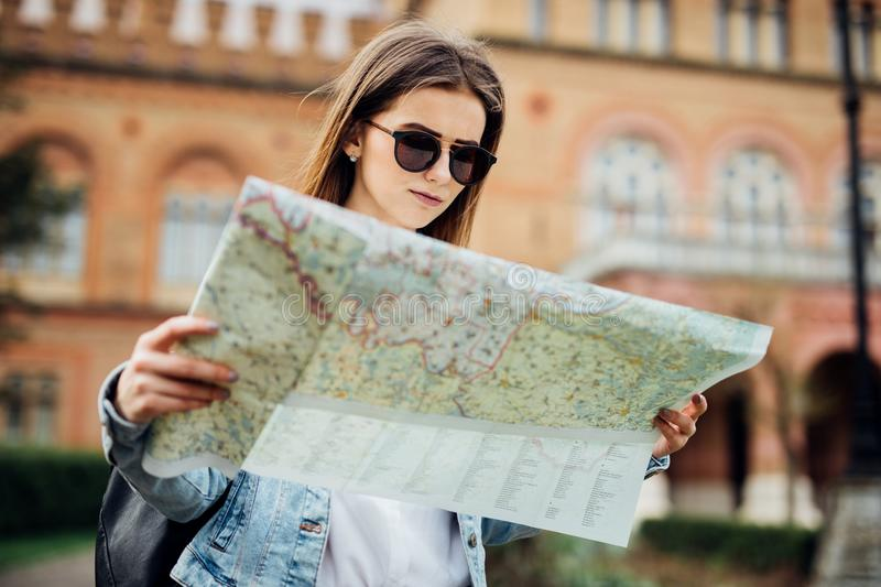 Cheerful young woman wanderer searching direction on location map while traveling abroad in summer. Happy female tourist searching. Cheerful woman wanderer royalty free stock photos