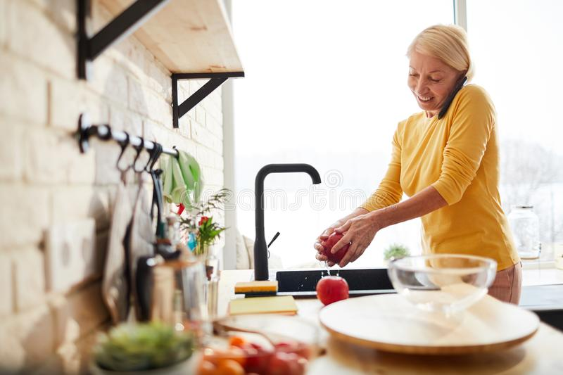 Cheerful woman washing fruit while talking on phone royalty free stock images