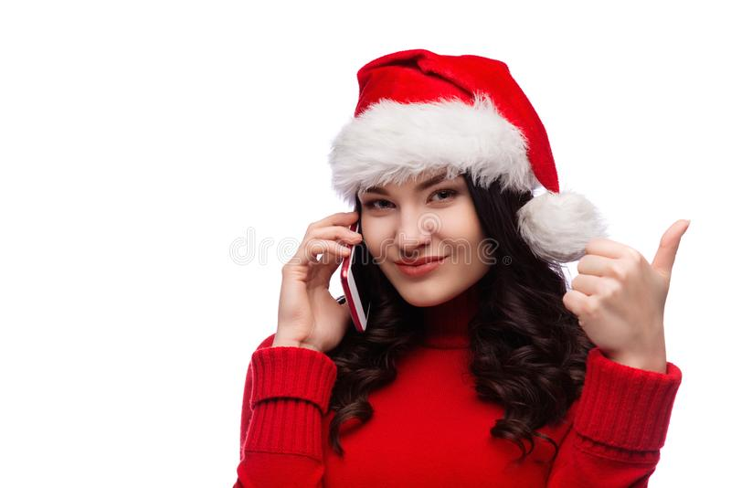 Cheerful woman wearing santa hat with exited face expression showing ok gesture and talking on phone, isolated royalty free stock photos