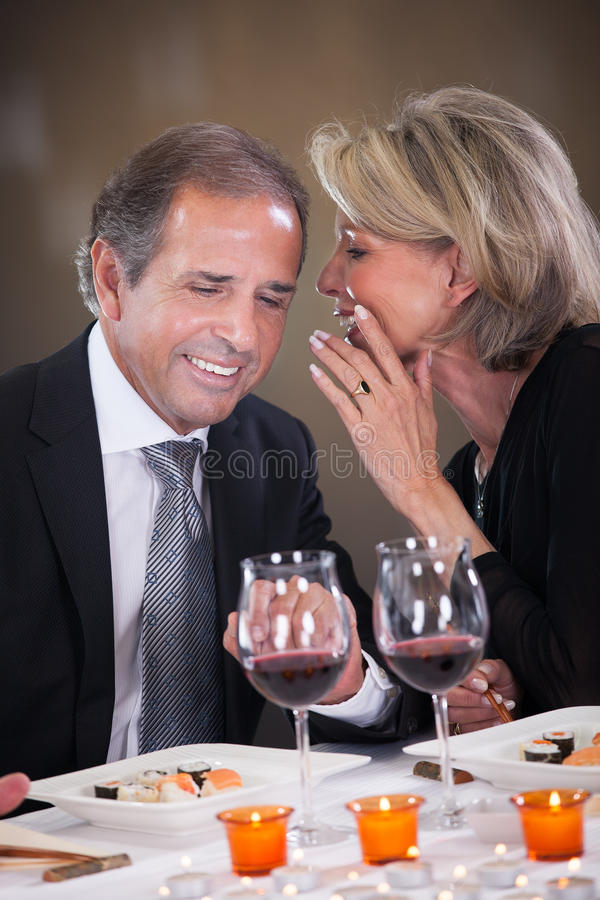 Cheerful Woman Whispering In Man's Ear. Cheerful Woman Whispering Something In Man's Ear In A Elegant Restaurant stock photography