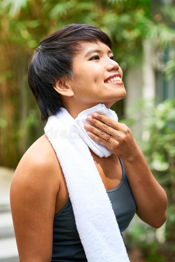 Cheerful woman wiping neck after training royalty free stock photo