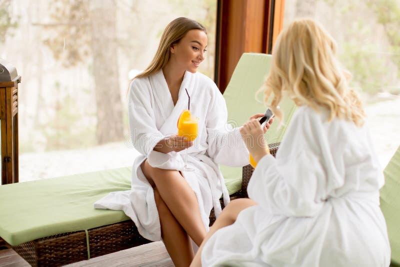Cheerful women in bathrobes drinking juice in spa center. Two cheerful young women in bathrobes drinking juice in spa center stock photo