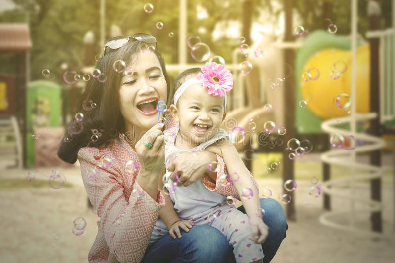 Cheerful woman blows soap bubbles with her child royalty free stock images