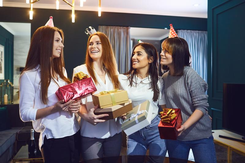 Cheerful women celebrating birthday at home. Group of cheerful beautiful women standing together with gifts while having birthday party stock image