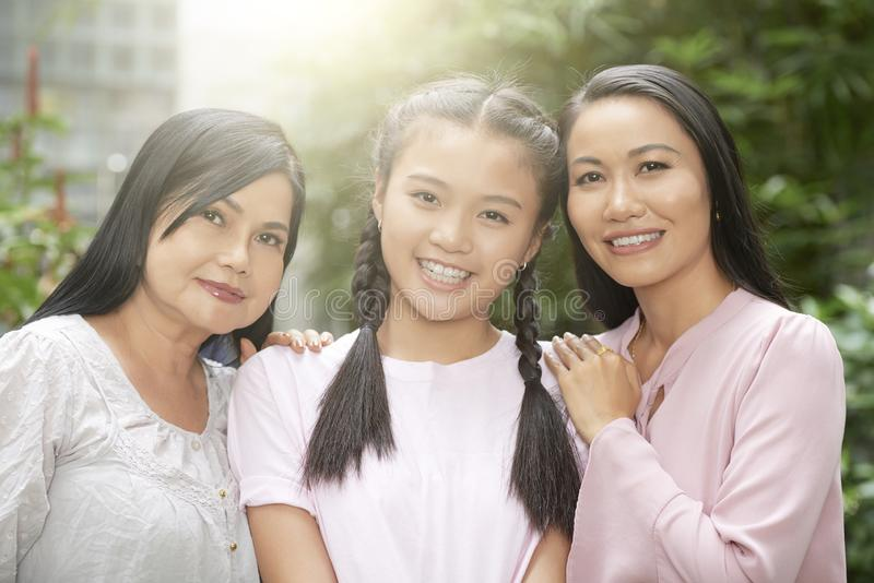 Cheerful women of different generations. Portrait of teenage girl with mother and grandmother embracing happily and looking at camera in sunlight stock photos