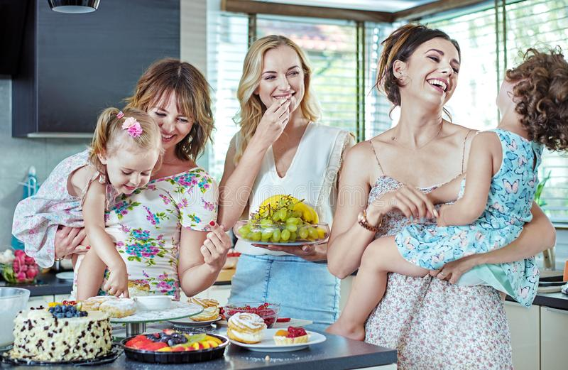 Cheerful women eating cakes and sweets with their children. Cheerful young women eating cakes and sweets with their children stock image