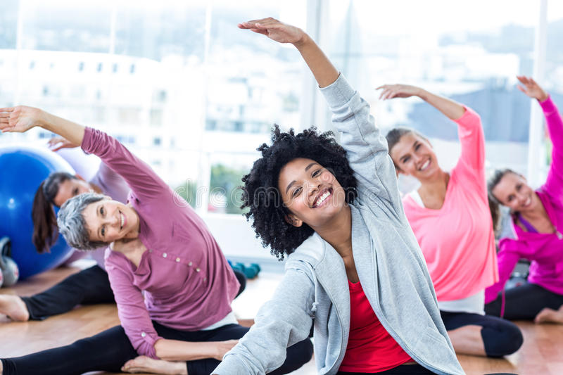 Cheerful women exercising with arms raised. In fitness studio royalty free stock photography