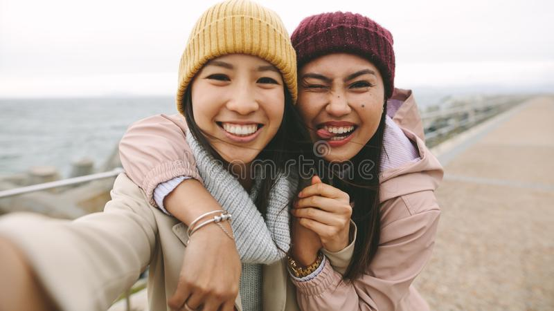 Cheerful women friends having fun standing outdoors stock image