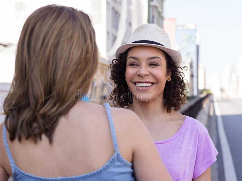 Cheerful women with hat talking and laughing in urban background royalty free stock photos