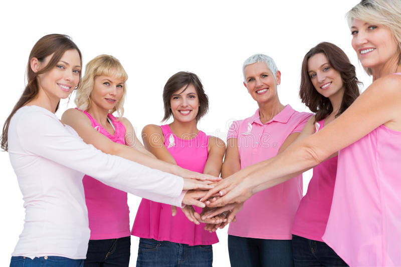 Cheerful women posing in circle holding hands looking at camera. Wearing pink for breast cancer on white background royalty free stock image