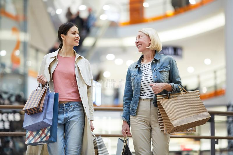Cheerful women sharing expressions from shopping stock image