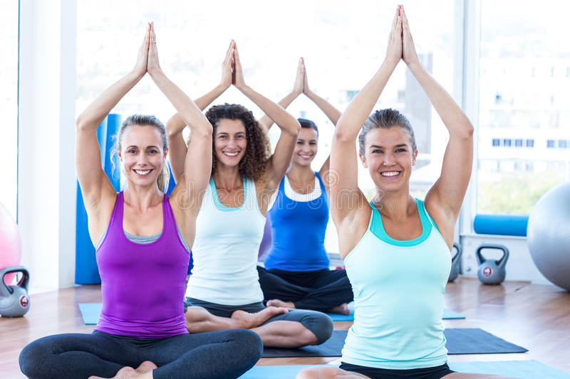 Cheerful women sitting with hands overhead in fitness studio. Portrait of cheerful women sitting on exercise mat with hands overhead in fitness studio royalty free stock image