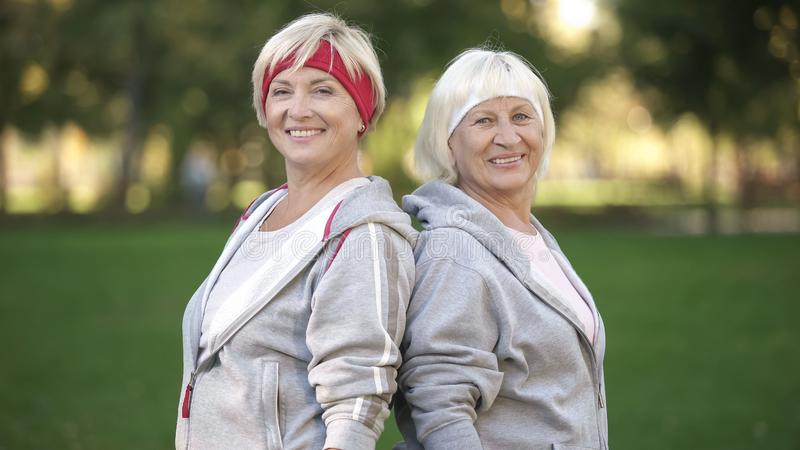 Cheerful women in sport suits smiling after workout in park, healthy lifestyle stock images