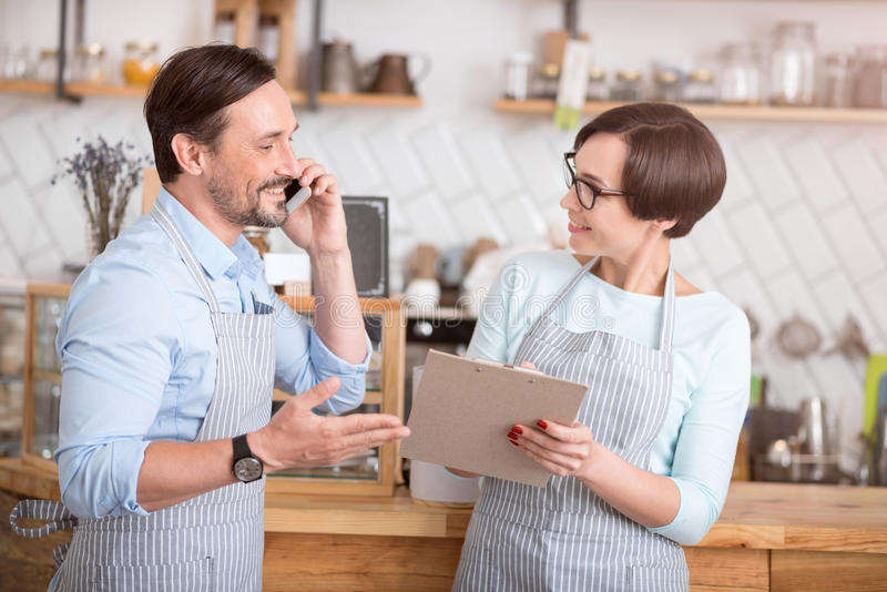 Cheerful workers communicating in cafe. Working. Positive and smiling cafe workers holding folder and talking per smart phone royalty free stock photography