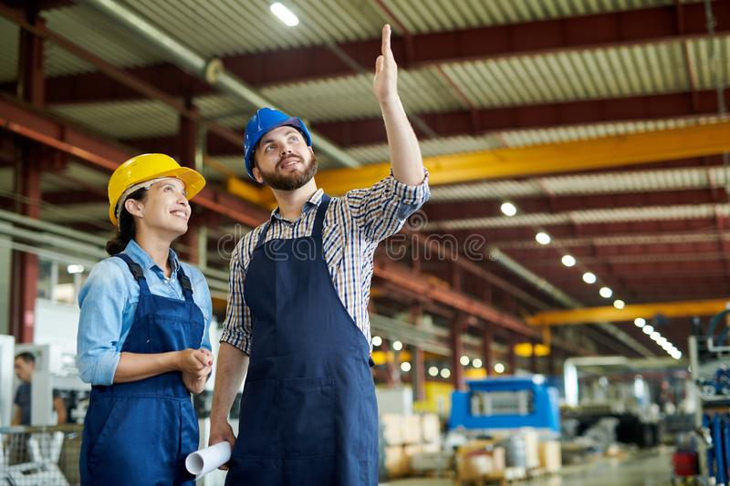 Cheerful Workers at Plant. Low angle portrait of two cheerful factory workers discussing production and smiling happily pointing up in workshop, copy space stock photography