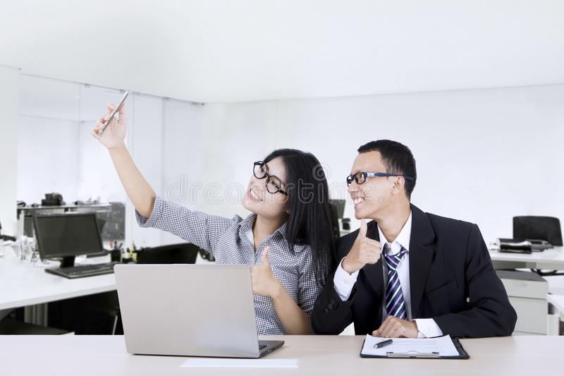 Cheerful workers taking selfie photo in office. Two young cheerful workers taking selfie photo with a mobile phone while showing thumbs up in the office royalty free stock image