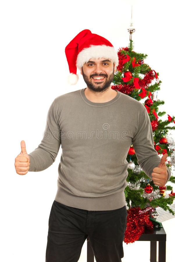 Cheerful Xmas man giving thumbs up. Cheerful Christmas man giving thumbs up in front of tree royalty free stock photography