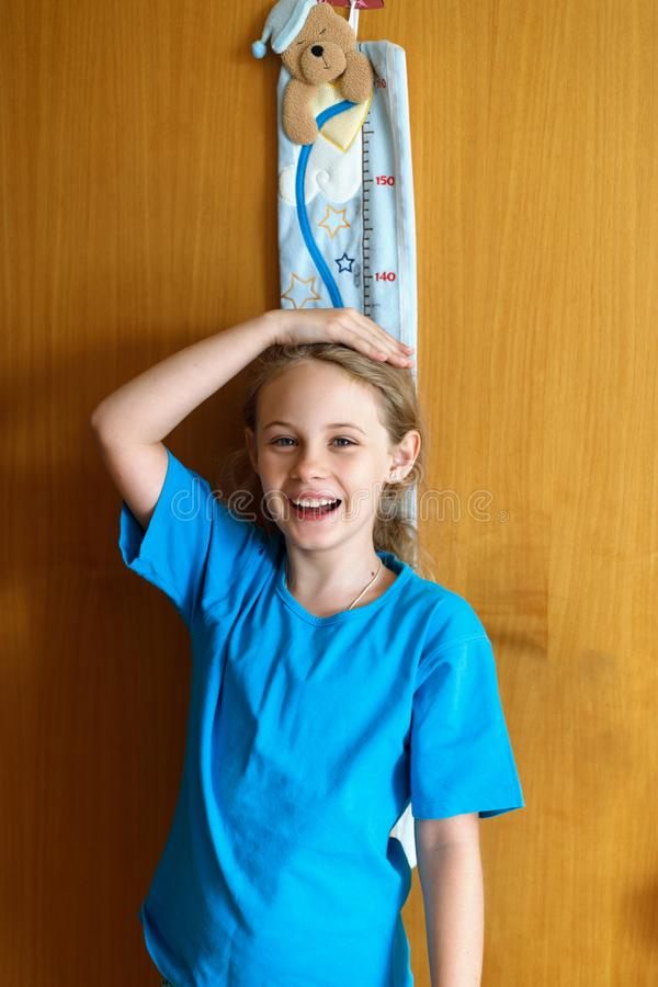 Cheerful 8 years old girl measures the growth on the wooden wall texture background stock images