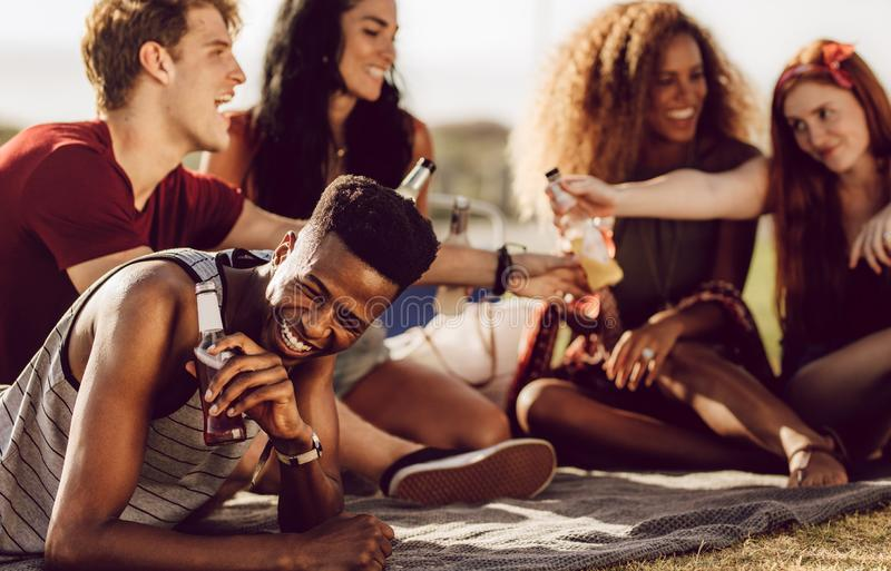Guy enjoying summer weekend with friends. Cheerful young african guy sitting with friends outdoors and laughing. Man enjoying summer weekend with friends royalty free stock images