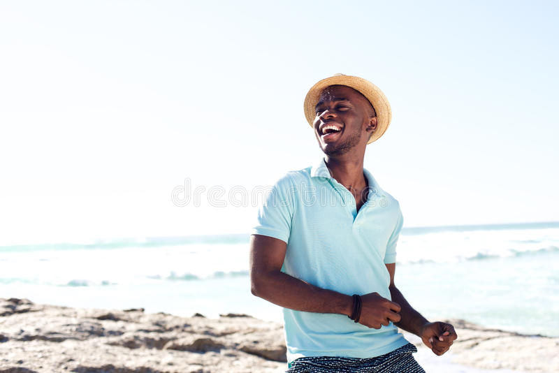 Cheerful young african man enjoying at the beach stock image