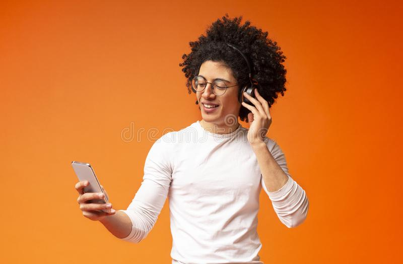 Cheerful young african man in headphones using music mobile application stock photography