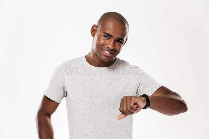 Cheerful young african man using watch. royalty free stock photo