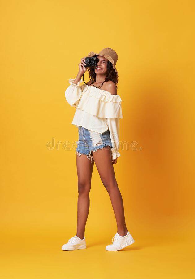 Cheerful young african woman dressed in summer clothes holding camera shooting over yellow background royalty free stock image
