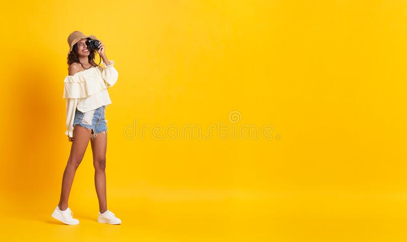 Cheerful young african woman dressed in summer clothes holding camera shooting over yellow background with copy space royalty free stock image