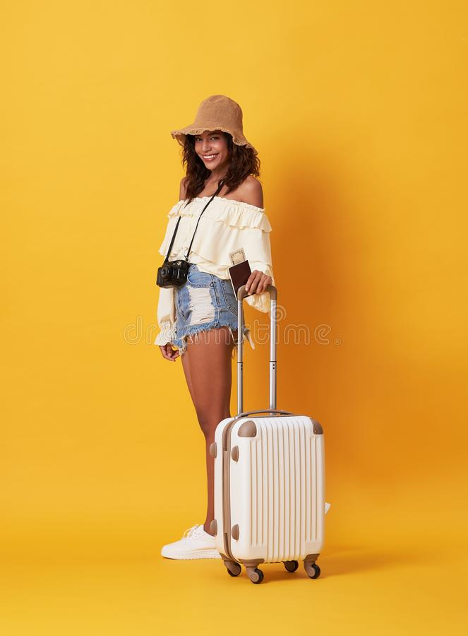 Cheerful young african woman dressed in summer clothes holding passport with money while standing with a suitcase isolated over. Yellow background royalty free stock photo