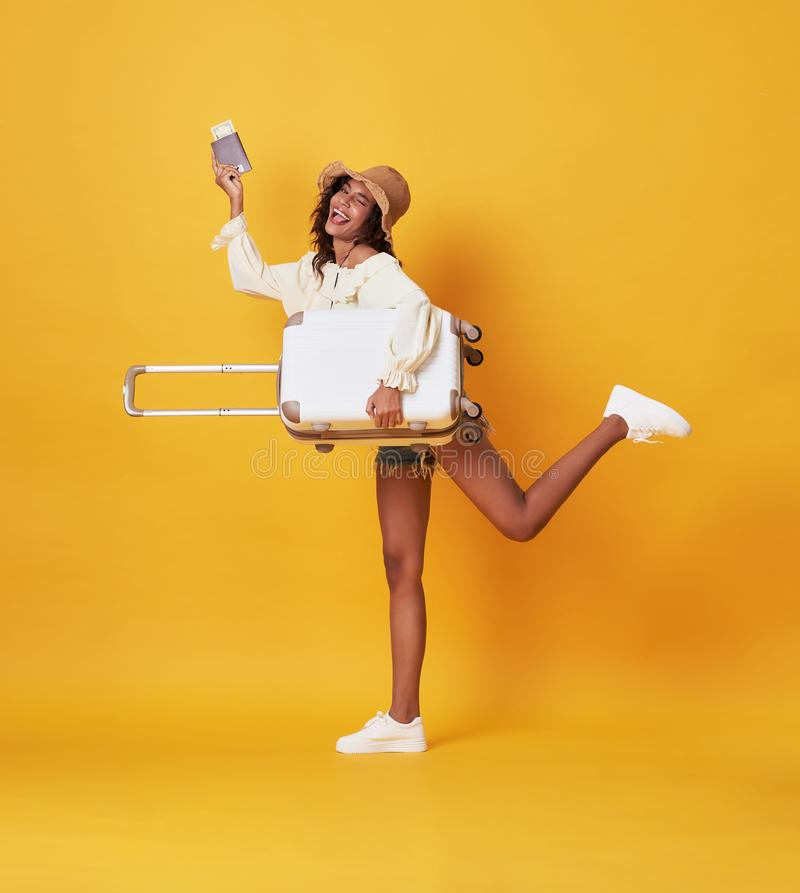 Cheerful young african woman dressed in summer clothes Holding a suitcase and passport and runing at copy space isolated over. Yellow background stock photography