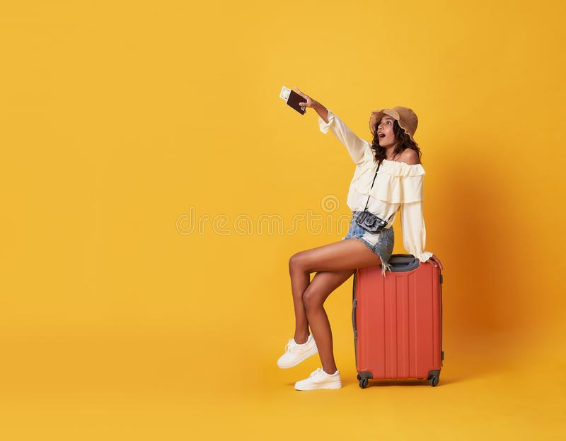 Cheerful young african woman dressed in summer clothes sitting on a suitcase and pointing finger at copy space isolated over. Yellow background stock photography