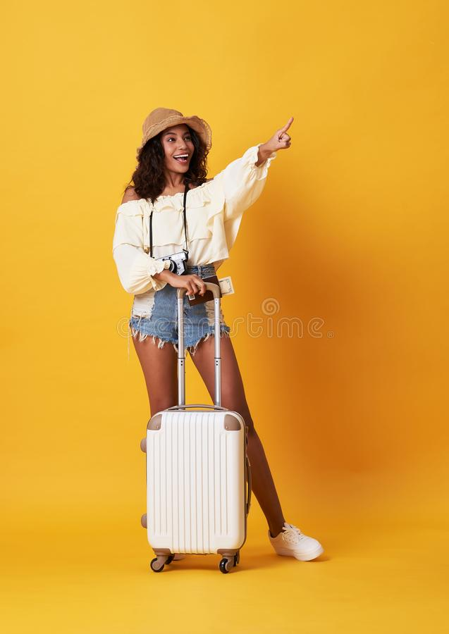 Cheerful young african woman dressed in summer clothes standing with a suitcase and pointing finger at copy space isolated over stock photography