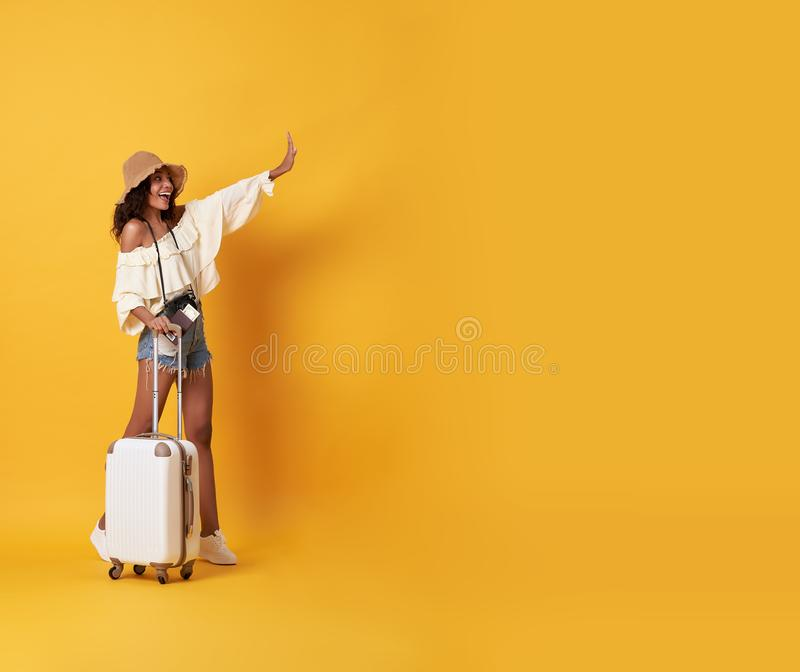 Cheerful young african woman dressed in summer clothes standing with a suitcase and say hello at copy space isolated over yellow. Background royalty free stock photos