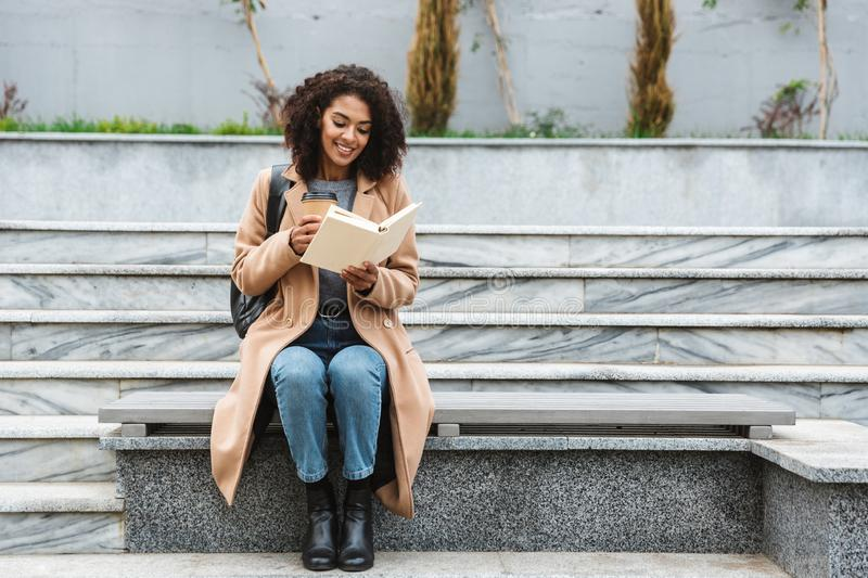 Cheerful young african woman wearing coat walking. Cheerful young african woman wearing coat sitting outdoors, holding takeaway coffee cup, reading a book stock image