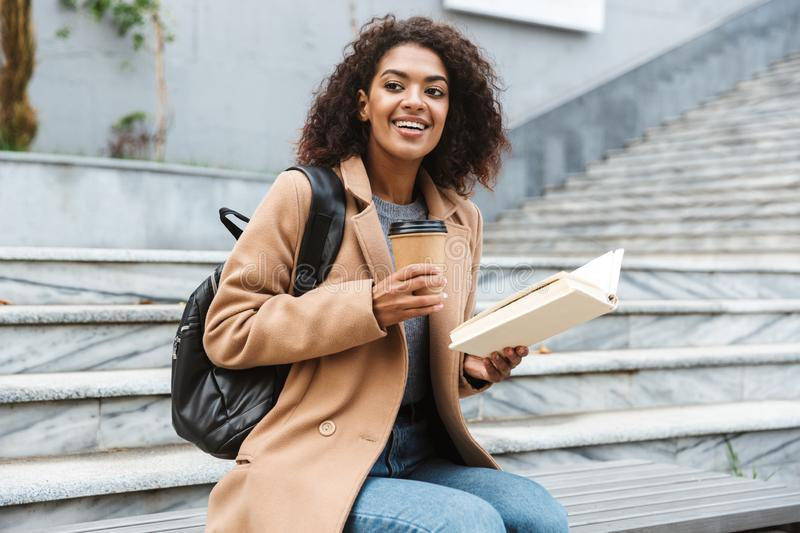 Cheerful young african woman wearing coat walking. Cheerful young african woman wearing coat sitting outdoors, holding takeaway coffee cup, reading a book royalty free stock photos