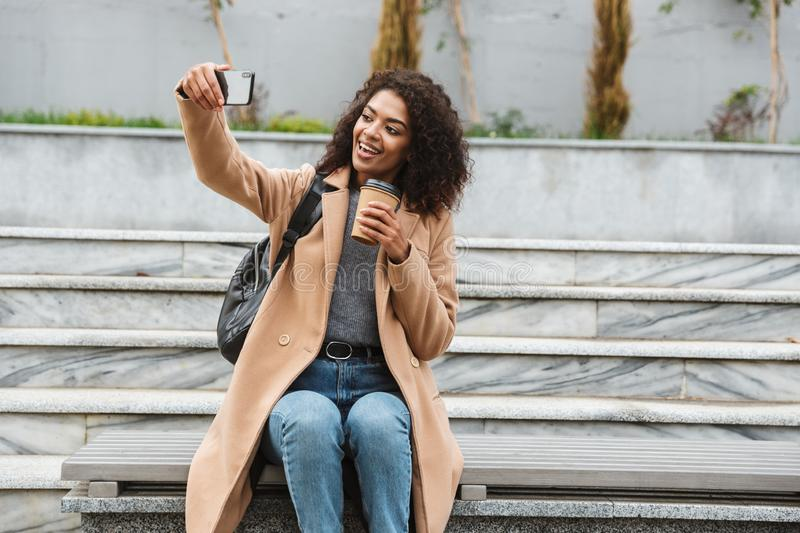 Cheerful young african woman wearing coat walking. Cheerful young african woman wearing coat sitting outdoors, holding takeaway coffee cup, taking a selfie stock photos