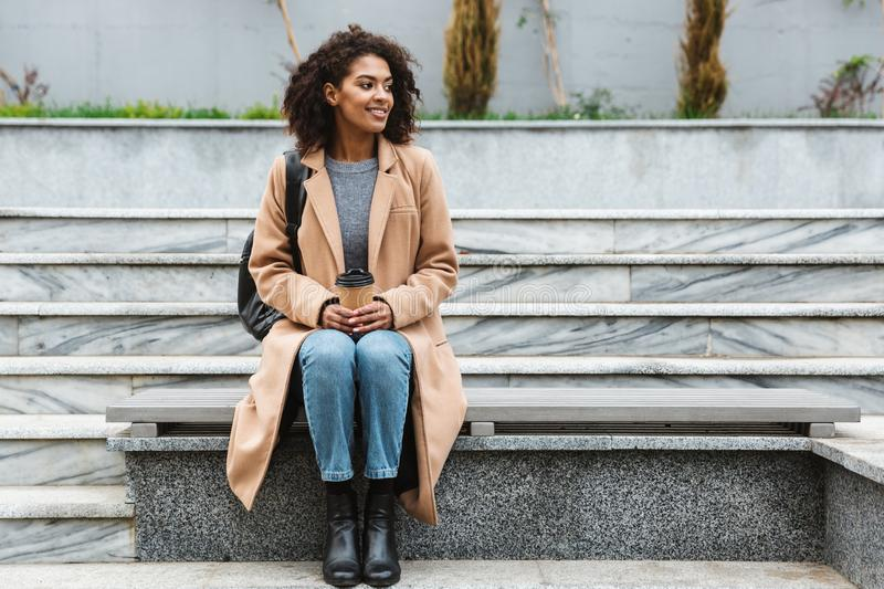 Cheerful young african woman wearing coat walking. Cheerful young african woman wearing coat sitting outdoors, holding takeaway coffee cup stock image