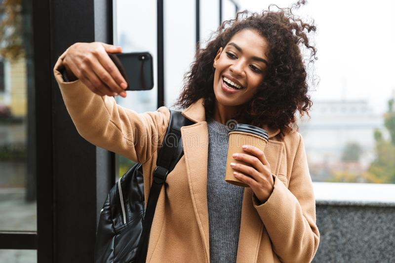 Cheerful young african woman wearing coat walking. Outdoors, holding takeaway coffee cup, taking a selfie royalty free stock images