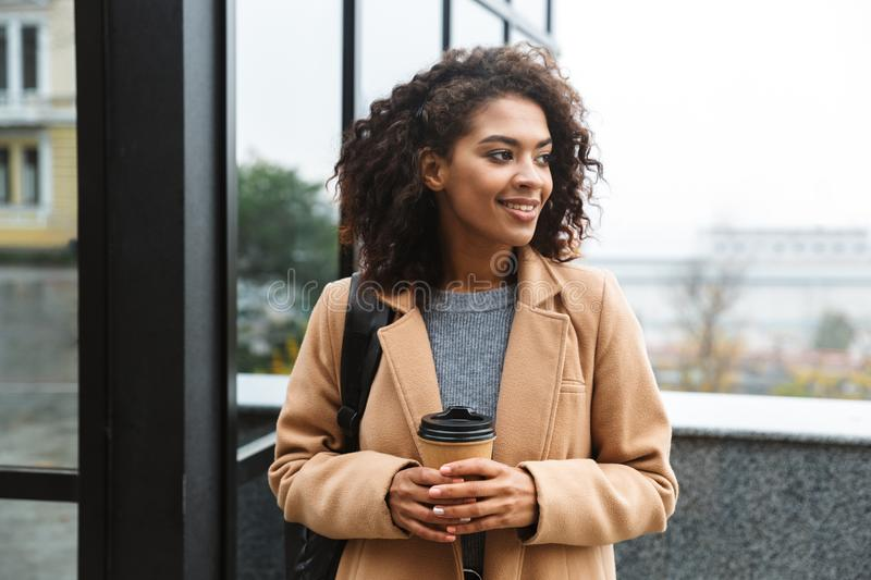 Cheerful young african woman wearing coat walking. Outdoors, holding takeaway coffee cup royalty free stock images
